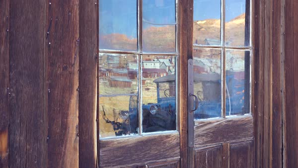 Reflection in old glass windows reveals the abandoned ghost town of Bodie, California. Royalty-free stock video