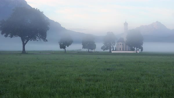 A traditional Bavarian church stands in the fog near the town of Schwangau, Germany. Royalty-free stock video