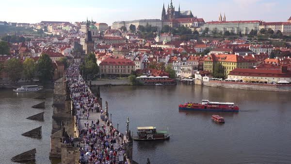 Beautiful day establishing shot crowds crossing the Charles Bridge over the Vltava River in Prague, Czech Republic. Royalty-free stock video