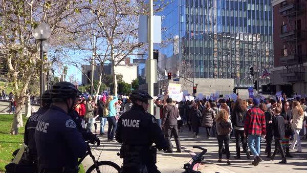Police keep a close eye on marching protestors at a rally against Donald Trump in downtown Los Angeles. Royalty-free stock video
