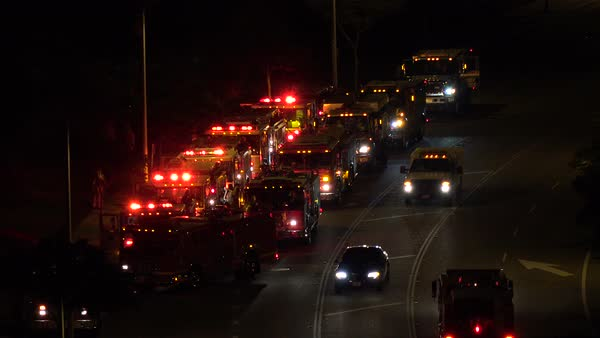 Fire trucks and emergency vehicles are lined up in a staging area at night during an emergency. Royalty-free stock video