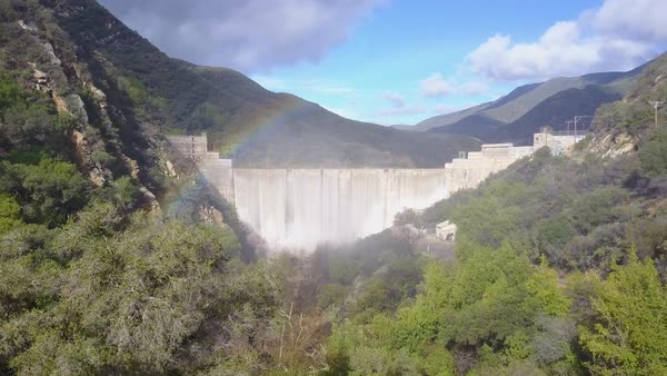 Aerial shot over a dam in full flood stage near Ojai California with rainbow Royalty-free stock video