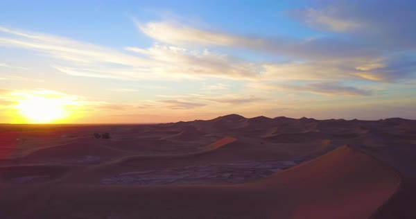 A remarkable aerial over desert sand dunes and a small village at sunrise in Morocco. Royalty-free stock video