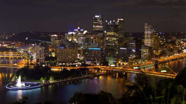 A colorful city 4K timelapse of Pittsburgh, Pennsylvania at night, featuring a busy highway with cars, boats traveling down the river, illuminated buildings and fast-moving clouds. Wide shot from above the city with no camera movement. Royalty-free stock video