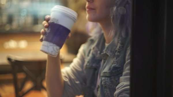 Medium close-up shot of a girl drinking a coffee while talking on the phone Royalty-free stock video
