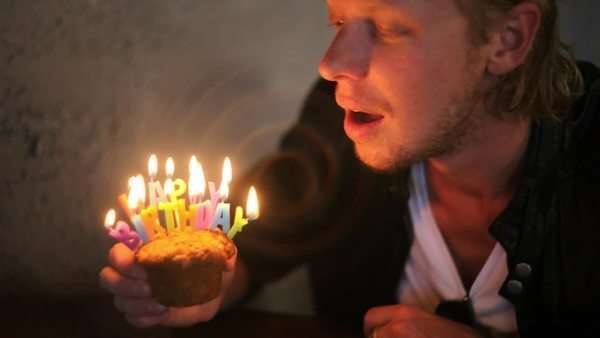 Close-up shot of man holding birthday muffin then blowing it out and taking a bite of it Royalty-free stock video