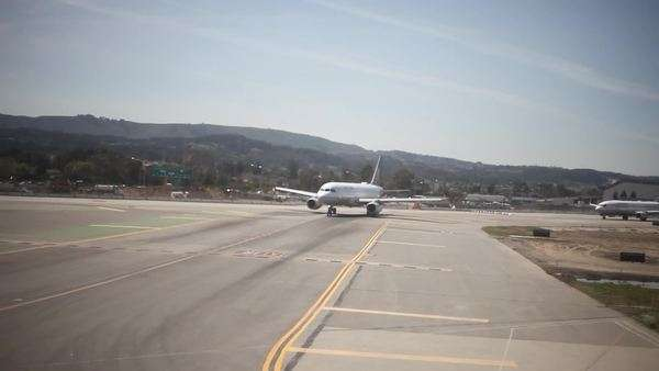 Long shot of airplanes turning onto runway seen from window Royalty-free stock video