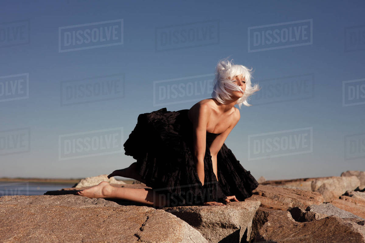 Woman kneeling on rocks Royalty-free stock photo