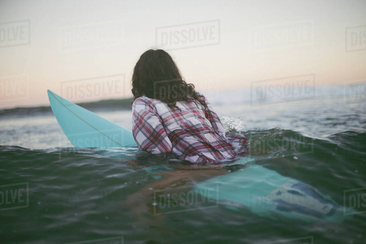 Rear view of a woman sitting on a surfboard in ocean Royalty-free stock photo