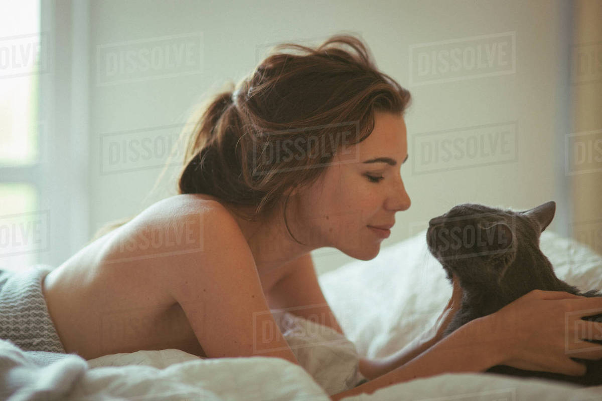 Close-up shot of a beautiful young woman lying on bed with cat at home Royalty-free stock photo