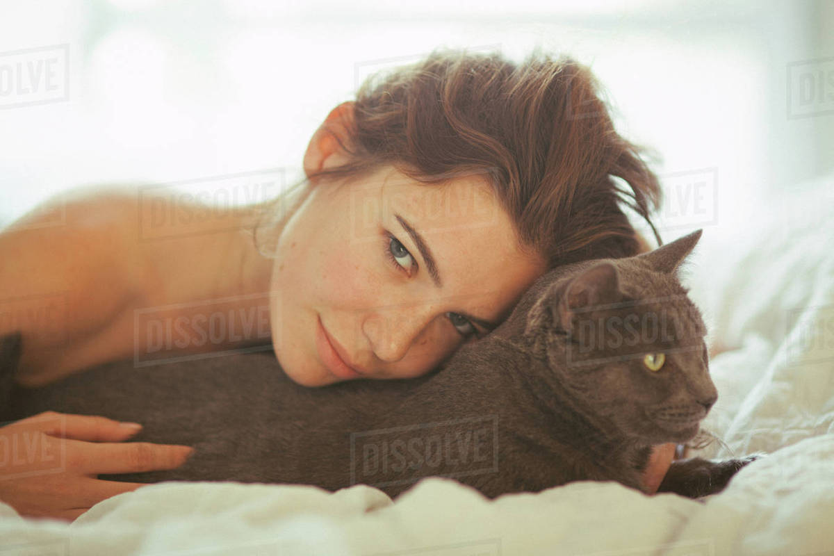 Portrait of a beautiful young woman lying on bed with cat at home Royalty-free stock photo