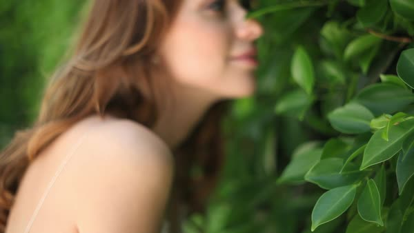 Close-up shot of women in white slip sniffing at green leaves Royalty-free stock video