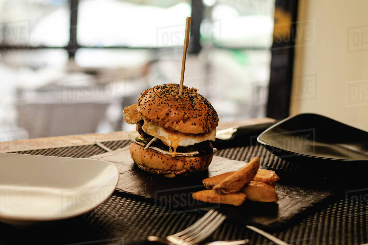 Burger with egg and fries served on restaurant Royalty-free stock photo