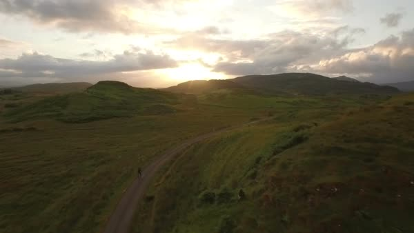 Drone shot of a man cycling along a quiet road in Scotland during sunrise Royalty-free stock video