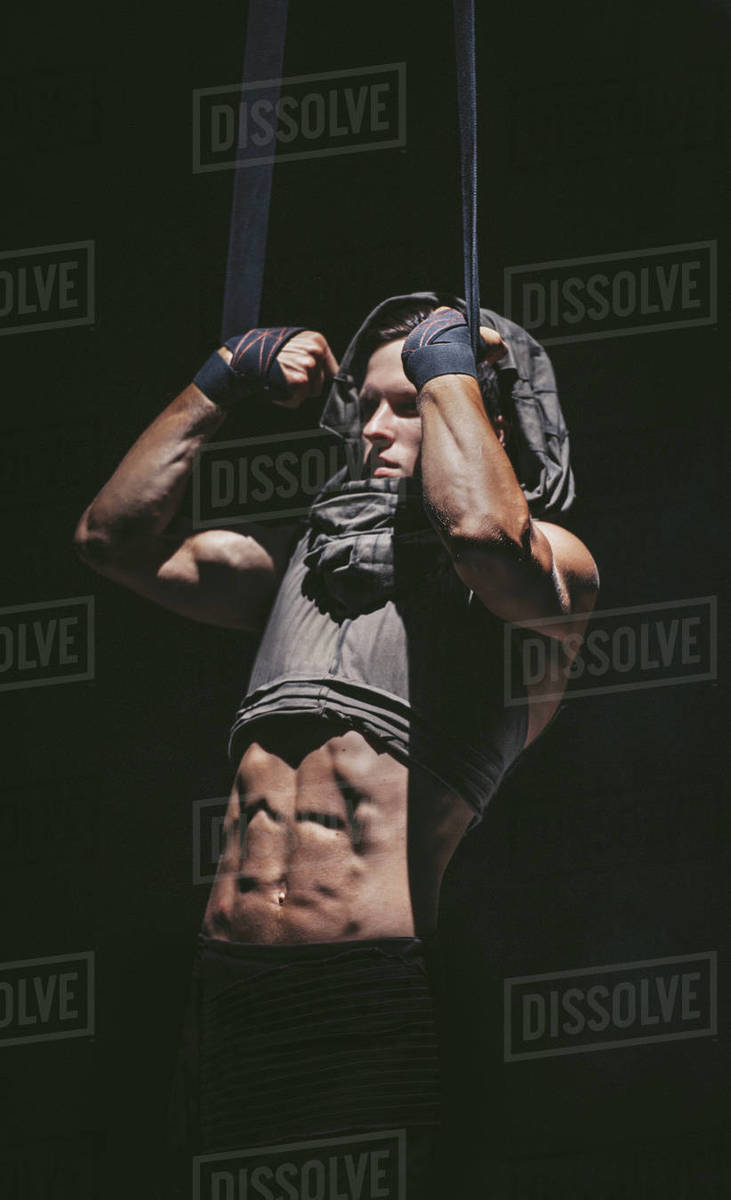 Young bodybuilder pull himself up on the ropes in projector light. Royalty-free stock photo