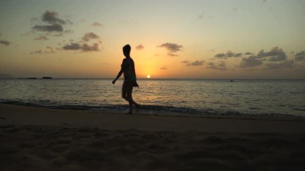 Hand-held shot of a woman walking on a beach at sunset Royalty-free stock video