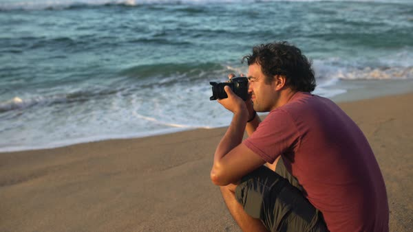 Hand-held shot of a man taking photos on a beach Royalty-free stock video
