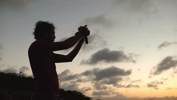 Low-angle shot of a man making a video at sunset Royalty-free stock video