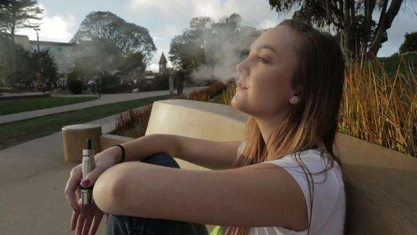 Medium shot of a woman smoking on a bench Royalty-free stock video