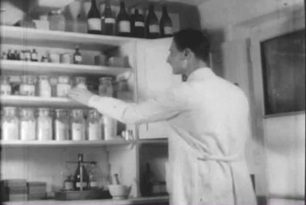 Two veterinarians in a lab: one weighs powders and drops chemical drops and the other checks a medical chart for a cow; as dairy cows are fed in their corral on a ranch or fundo in Chile in 1949. Royalty-free stock video