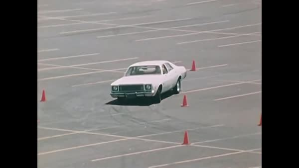 Drivers practice offensive driving techniques in a parking lot, in 1976. Royalty-free stock video