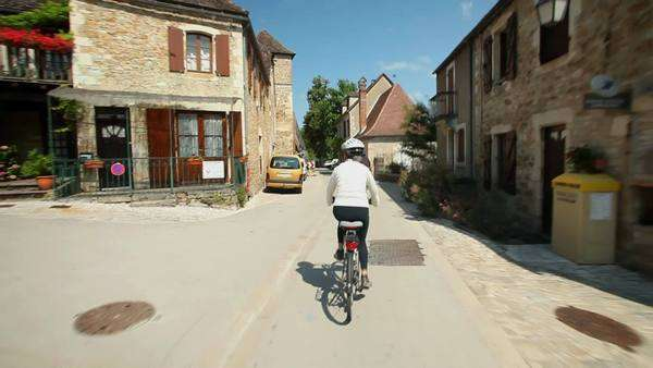 Slow motion - Retired couple cycling on road in village in France Royalty-free stock video