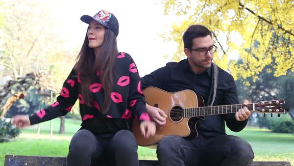 Tilt shot of beautiful young couple playing guitar and singing while sitting on a tree in park, graded Royalty-free stock video