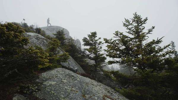 Man walks out on rock in fog on top mountain Royalty-free stock video