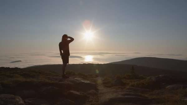 Person stands on top of mountain at sunrise points to the distance Royalty-free stock video