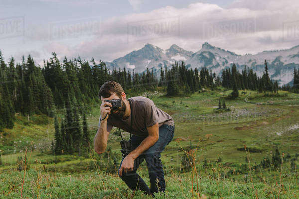 Man crouches to take a picture in front of beautiful scenary Royalty-free stock photo