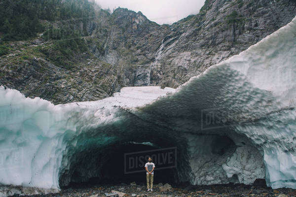 Man poses in front of large ice cave Royalty-free stock photo
