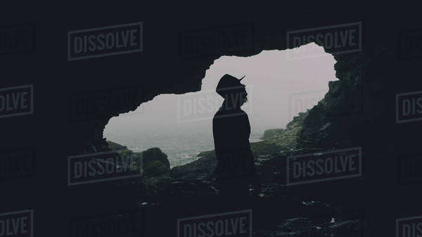 Man looking upward silhouetted in cave by ocean Royalty-free stock photo