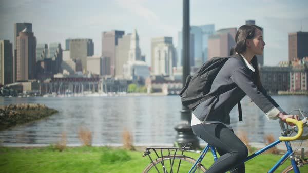 Young woman riding bicycle in front of Boston skyline Royalty-free stock video
