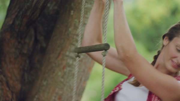 A young woman swinging on rope ladder and smiling Royalty-free stock video