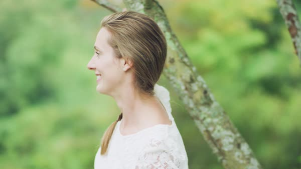Portrait of a young woman standing near tree trunk and smiling Royalty-free stock video