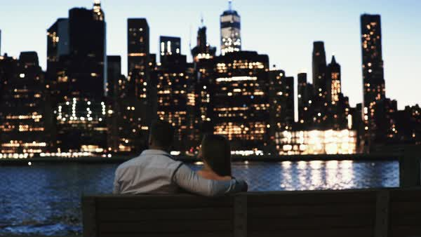 Tilt-down shot of a couple sitting on a bench along East River Royalty-free stock video