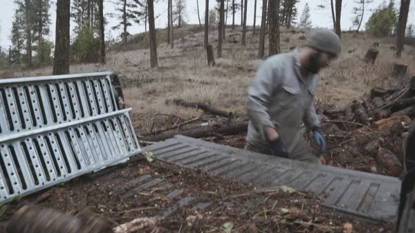 Hand-held shot of a man putting logs on a pickup truck Royalty-free stock video