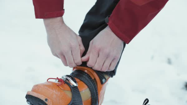 Tilt-down shot of a ski mountaineer adjusting his clothes Royalty-free stock video