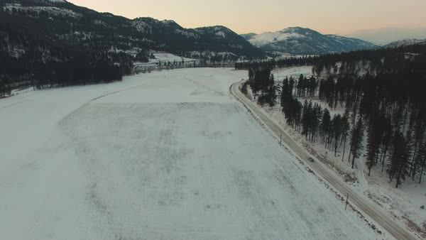 Aerial shot of a car driving alongside a frozen river Royalty-free stock video