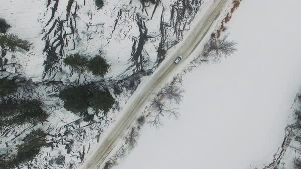 Aerial tracking shot of a car driving alongside a frozen river Royalty-free stock video