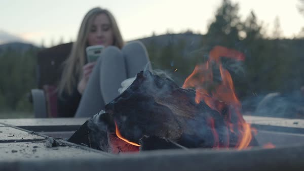 Hand-held shot of a young woman using her smartphone by a campfire Royalty-free stock video