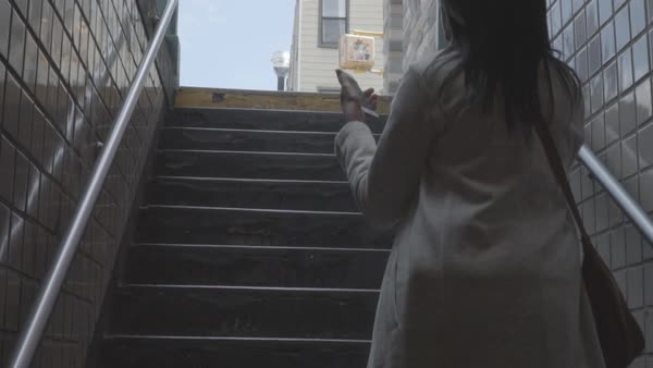 Slow motion shot of a woman walking up stairs with a cell phone in her hand Royalty-free stock video