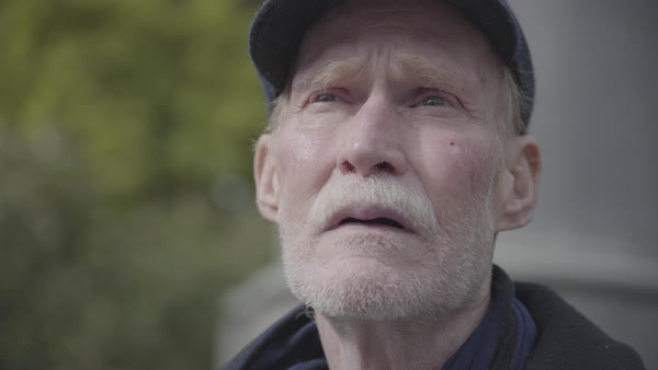 Hand-held shot of an elderly man looking around in a park Royalty-free stock video