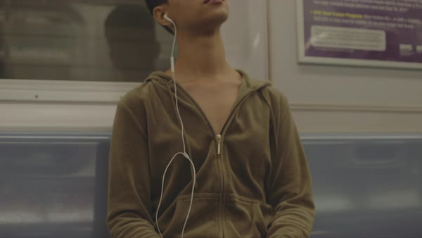 Tilt shot of a woman listening music on mobile phone on a subway Royalty-free stock video