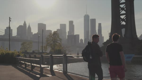 Tracking shot of two young men walking under a bridge in New York Royalty-free stock video