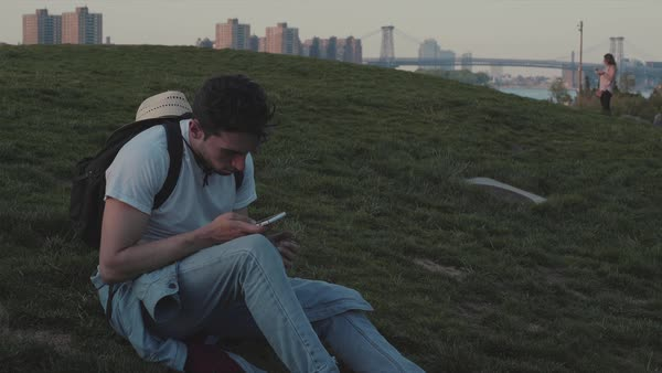Hand-held shot of a young man using a smartphone outside on a grassy hill Royalty-free stock video