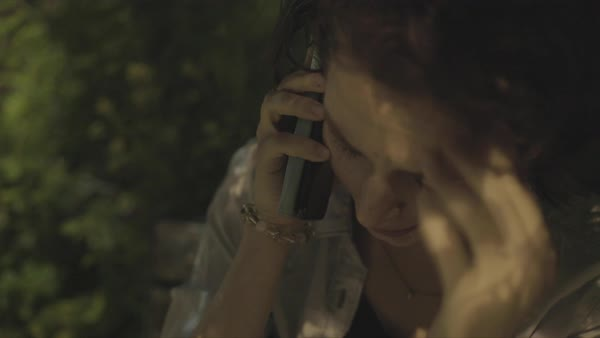 Hand-held shot of an upset young woman talking on phone outdoors at night Royalty-free stock video