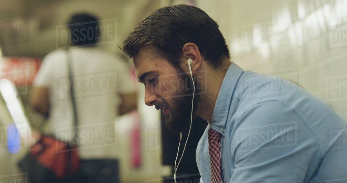 Smiling businessman wearing earphones listening to music while sitting at subway station Royalty-free stock photo
