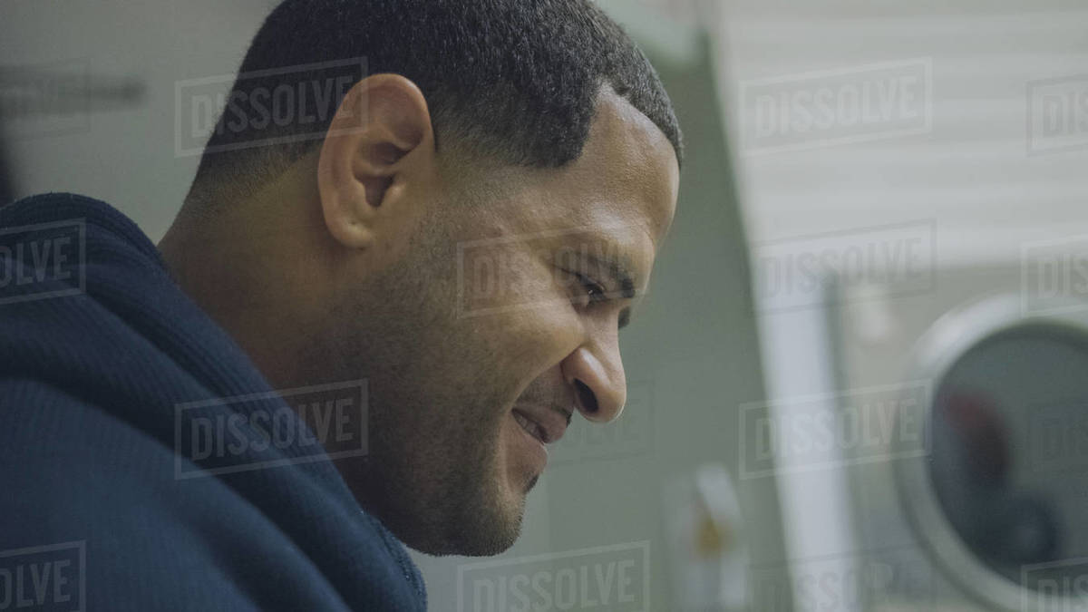Close-up shot of a smiling man sitting in laundromat Royalty-free stock photo