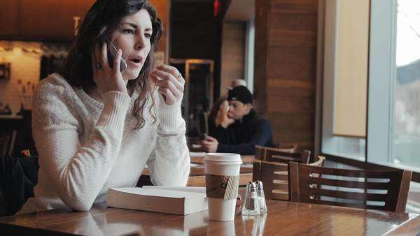 Beautiful girl talking on phone in coffee shop Royalty-free stock video